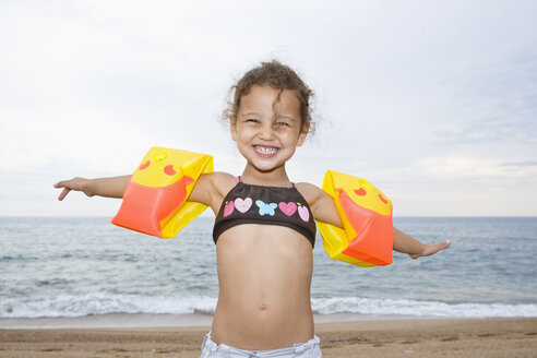 France, Corsica, Girl (2-3) wearing armbands on beach, smiling, portrait - SSF00055