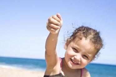 France, Corsica, Girl (2-3) holding sand, smiling, portrait - SSF00052