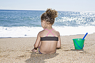 France, Corsica, Girl (2-3) siting on beach, rear view - SSF00049