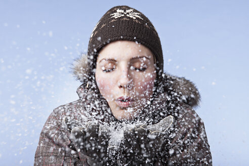 Young woman blowing snow, close-up - SSF00043