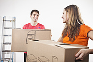 Young couple carrying cardboard boxes, smiling - SSF00037
