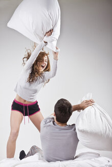 Young couple having pillow fight on bed - SSF00022