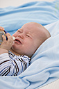 Baby boy (6-11 months) holding baby bottle, crying - SMOF00412