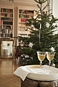 Wine glasses on table with christmas tree and bookshelf in background - NHF01215