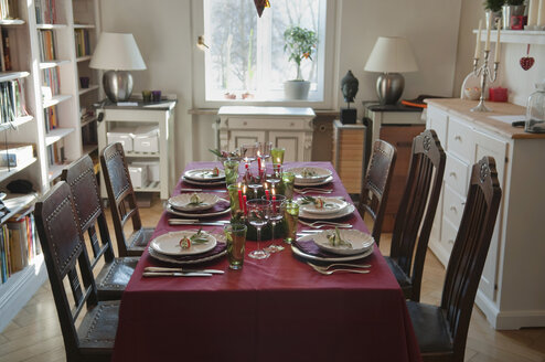 Place setting on dining table with bookshelf in background - NHF01209