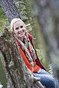 Austria, Obertauern, Woman sitting on tree trunk, smiling, portrait - HHF03274