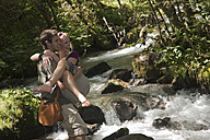 Austria, Steiermark, Man carrying woman and crossing stream, smiling - HHF03259