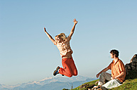 Man sitting, woman jumping in the air, arms up, smiling. - HHF03235