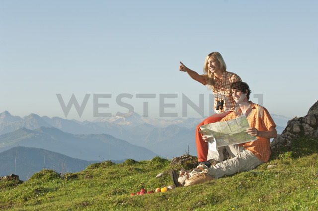 Young couple sitting on mountaintop, man holding map, smiling. - HHF03232