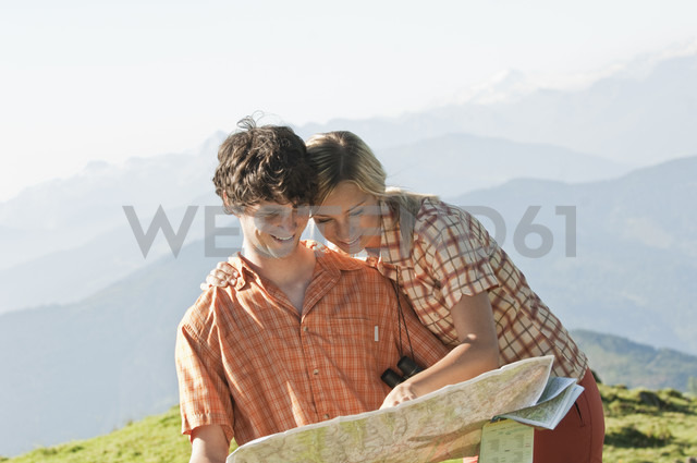 Young couple looking at a map on a mountaintop, smiling. - HHF03229