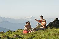 Young couple sitting, woman holding binoculars. - HHF03226