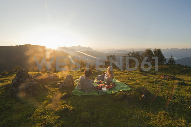 Young couple lying on blanket, looking at view. - HHF03211