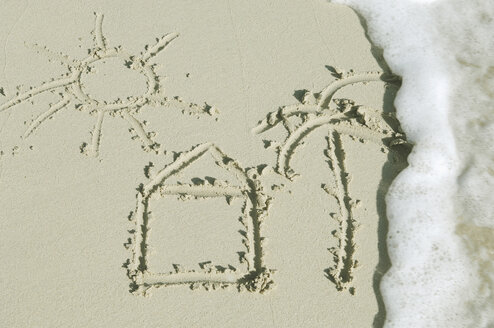 House, tree and sun drawn in sand on beach by sea. - CRF01852