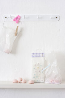 Pastries in plastic bags hanging on hook rack - COF00140