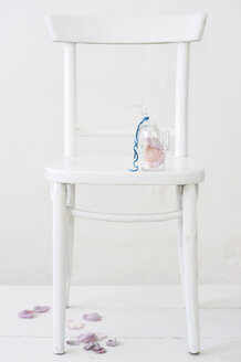 Sugared rose petals in glass on chair - COF00131