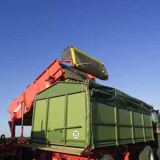 Germany, Hessen, Combine harvester loading potatoes into truck - AKF00157