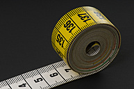 Rolled up measure tape on black background - AWDF00518