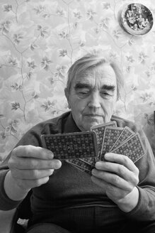 Senior man holding and playing cards - WV00036