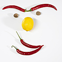 Chilli and nutmeg forming human face on white background, close-up - SRSF00060