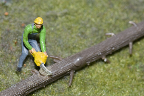Figurine of lumberman cutting tree trunk with electric saw - AWDF00528