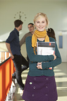 Germany, Leipzig, Young woman holding book with students standing in background - BABF00599