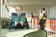 Germany, Leipzig, Woman reading book in hallway, students standing in background - BABF00593