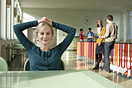 Germany, Leipzig, Woman sitting in hallway, students standing in background - BABF00590
