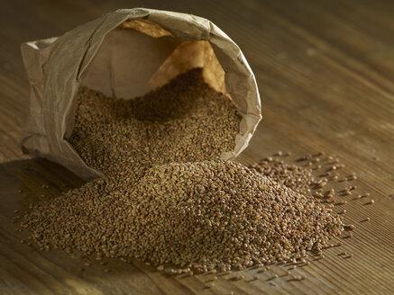 Alfalfa seeds spilling on wooden surface - SRSF00192