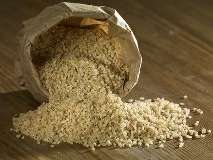 Bulgur wheat grain spilling on wooden surface - SRSF00183