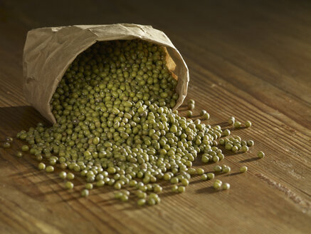 Green mung beans spilled on wooden surface - SRSF00150