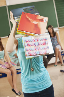 Germany, Emmering, Teenage girl with falling books from head - RNF00326