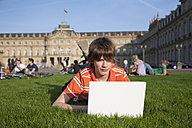 Germany, Stuttgart, Boy lying in palace yard and using laptiop - WDF00747