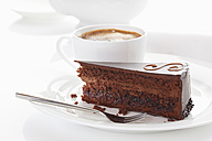 Slice of Sacher cake in plate with coffee cup in background - 13328CS-U