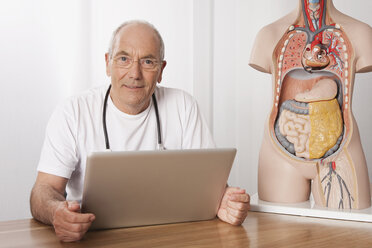 Germany, Munich, Doctor with laptop and human body figurine - WESTF14853