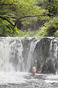 New Zealand, North Island, Mature woman taking a bath in hot spring kerosin creek - GWF001254