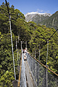 New Zealand, South Island, Woman standing on swing bridge - GWF001278