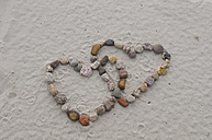 Germany, Northsea, Amrum, Stones in shape of heart on sand, close-up - AWDF000602