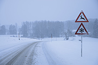Germany, Bavaria, Moerlbach, View of country road covered in snow with sign board - TCF001340
