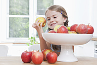 Germany, Munich, Girl (6-7) taking apple from bowl - RBF000301