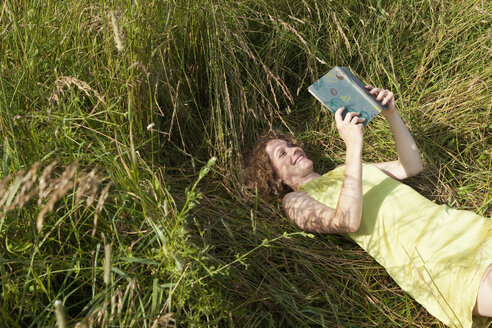 Germany, Munich, Woman lying on grass and reading book - LDF000889