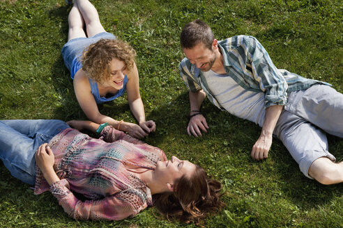 Germany, Munich, Man and woman lying on grass and smiling - LDF000883