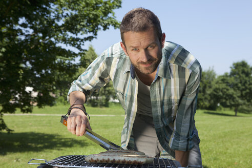 Germany, Munich, Man preparing sausages on brabecue grill - LDF000871