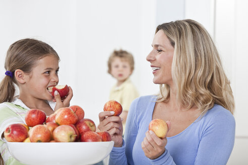Mother and daughter eating apple with son in background - LDF000834