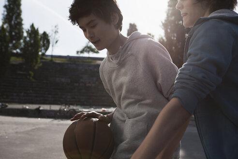 Germany, Berlin, Teenage boys playing basketball in playground - WESTF015330