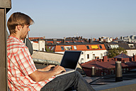 Germany, Bavaria, Munich, Young man with laptop on rooftop - SKF000402