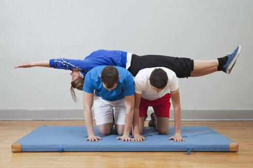 Germany, Berlin, Man balancing woman in gym on mat - BAEF000141