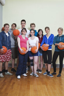 Germany, Berlin, People standing and holding basketball, portrait - BAEF000162