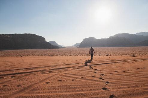 Jordan, Wadi Rum, Man walking through desert - NHF001237