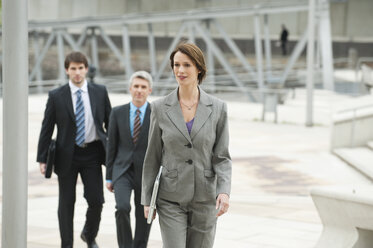 Germany, Hamburg, Businesswoman walking with business people in background - WESTF015446