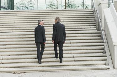 Germany, Hamburg, Businessmen climbing steps together - WESTF015476